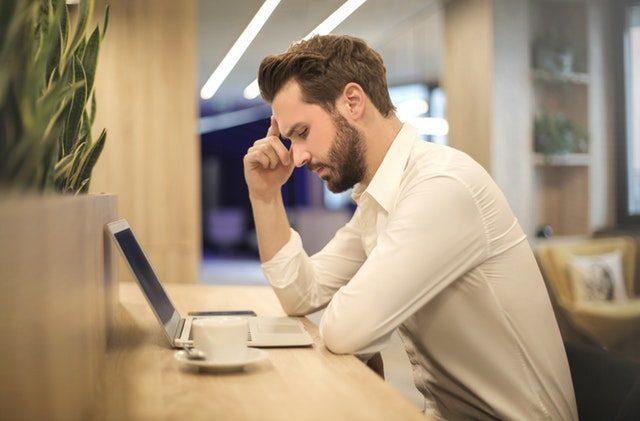 Man Thinking and Looking at Computer